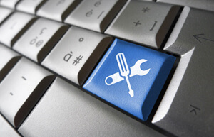 Assistance and computer service concept with toolkit icons and symbol on a blue laptop computer key for website and online business.